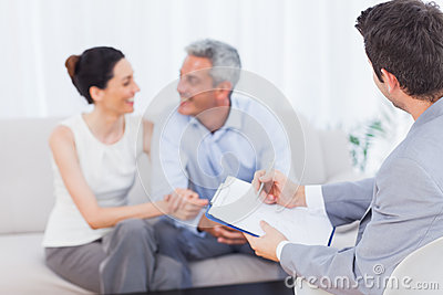 Couple speaking while salesman is holding contract
