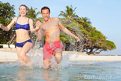 Couple Splashing In Sea On Tropical Beach Holiday