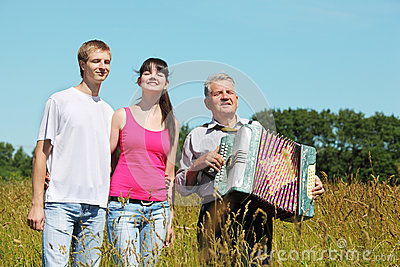 Couple stand near grandfather with accordion
