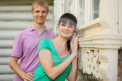 couple stand near wooden village house