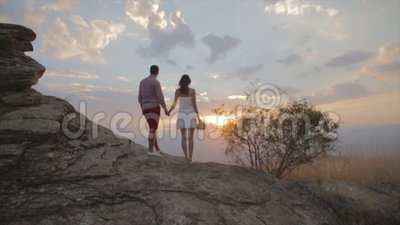 Couple stand on rock and watching sunset on top of the mountain. Girl is having flower in her hand stock video