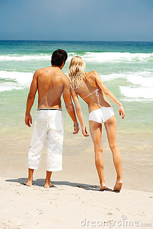 Couple standing on the beach looking at the ocean