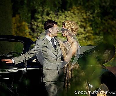 Couple standing near convertible