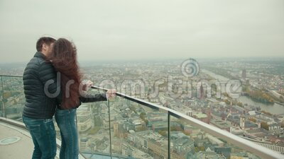 Couple is standing on roof of high building of skyscraper in city of megapolis. Girl is standing near transparent fence on roof of high building of skyscraper stock footage