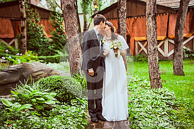 couple standing together in forest against wooden