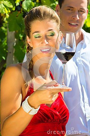 Couple standing at vineyard and drinking wine