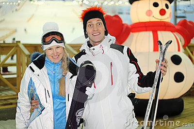 Сouple stands with skis in indoor ski