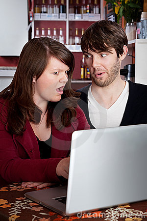 Couple staring in disbelief at a computer laptop