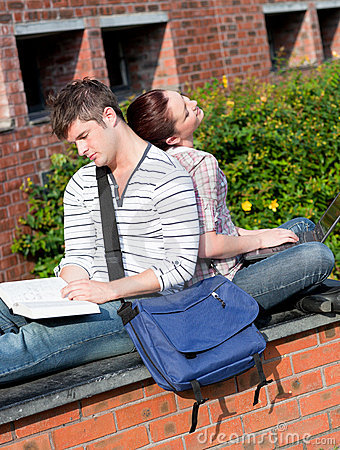 Couple of students using laptop and reading book