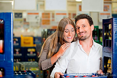 Couple in supermarket buying beverages