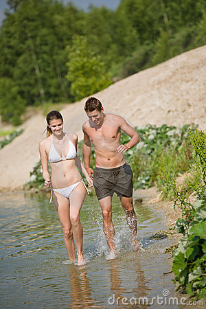 Couple in swimwear jogging at lakeside
