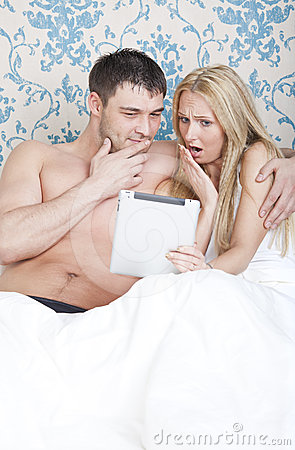 Couple with tablet computer in bed