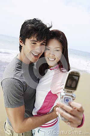 ... middle aged couple taking self-portrait through cell phone on beach