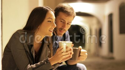 Couple talking and drinking coffee in the night. Happy couple talking and drinking coffee in the night in the street stock video footage