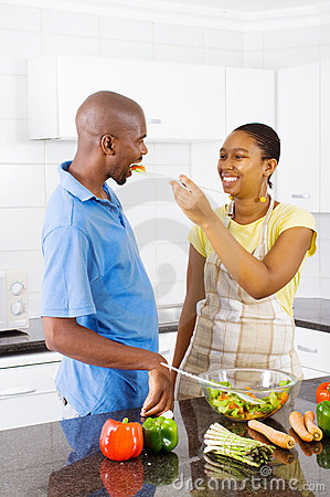 Couple tasting food in kitchen