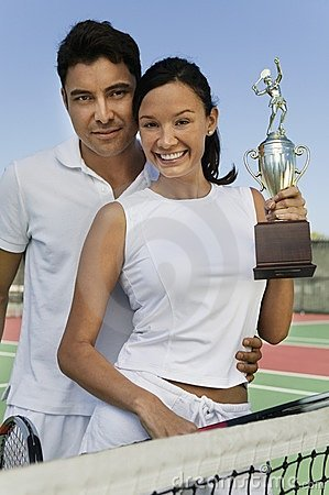 Couple at tennis court holding trophy