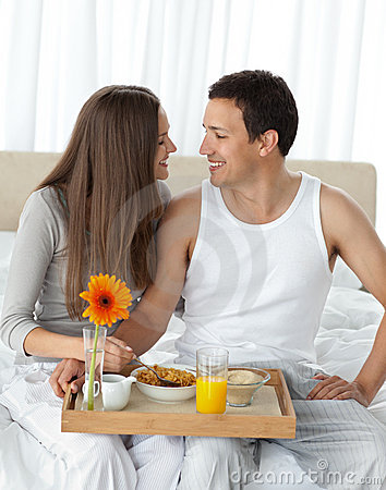 Couple with their breakfast on the bed