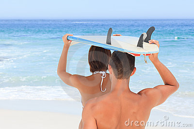 Couple with their surfboard