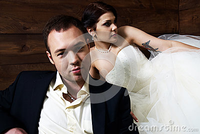 Couple in their wedding clothes in barn with hay