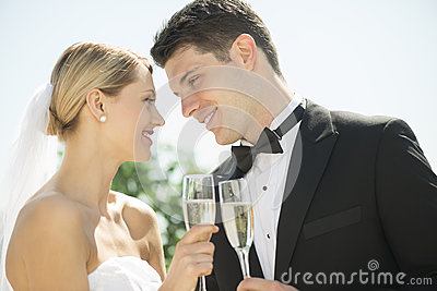 Couple Toasting Champagne Flutes Against Sky