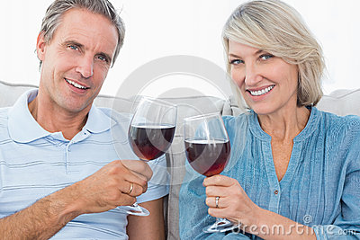 Couple toasting with red wine on the sofa smiling at camera