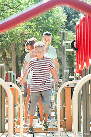Couple together with teenager overcoming the obstacle course