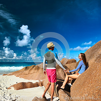 Couple at tropical beach wearing rash guard