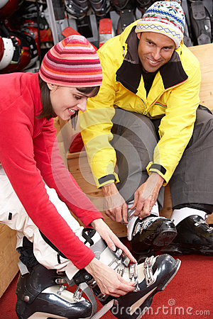 Couple On Trying On Ski Boots In Hire Shop