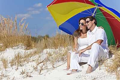 Couple Under Colorful Umbrella on Beach