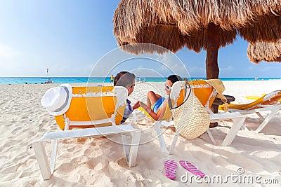 Couple under parasol at Caribbean Sea