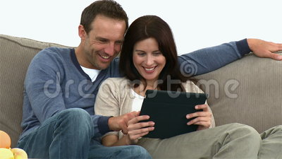 Couple using a computer tablet sitting on the sofa Stock Photo