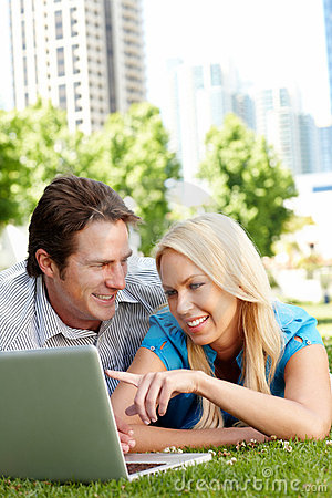 Couple using laptop in city park