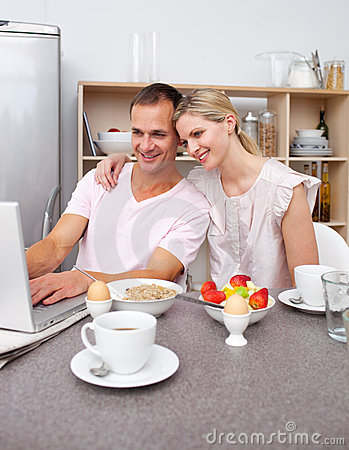 Couple using a laptop while having breakfast