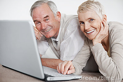 Couple using a laptop while lying on the floor