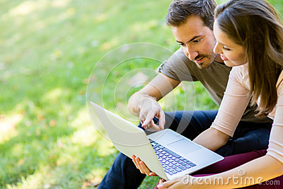 Couple using a laptop outdoors