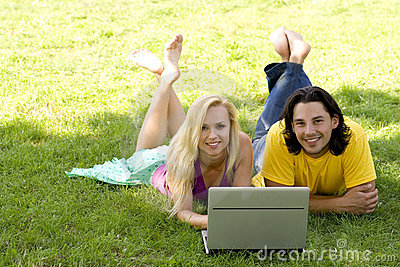 Couple using laptop outdoors