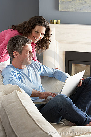Couple Using Laptop Relaxing Sitting On Sofa