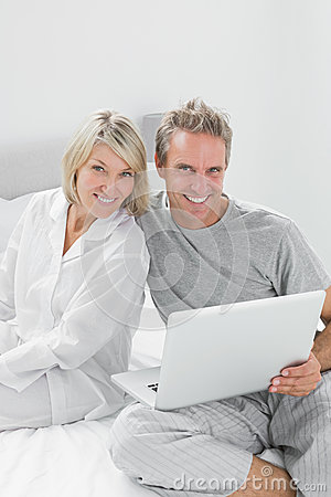 Couple using laptop sitting on bed looking at camera