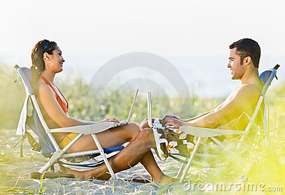 Couple using laptops at beach