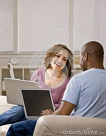Couple using laptops in livingroom