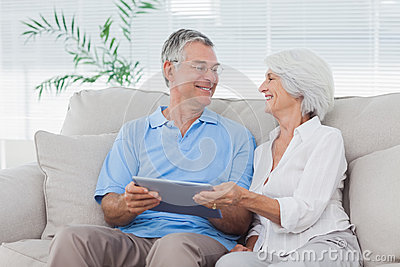 Couple using a tablet pc sitting on the couch