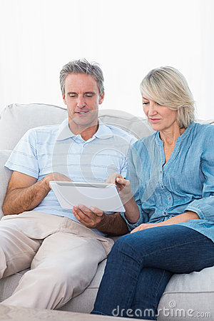 Couple using tablet pc together on the sofa