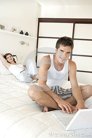 Couple Using Techno on Bed