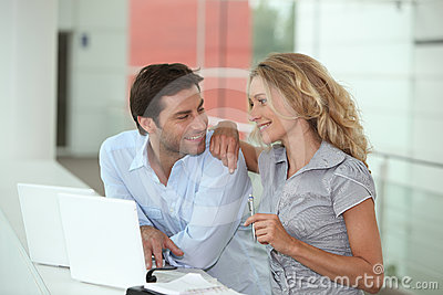 Couple using two laptops
