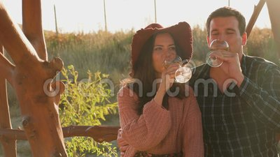 Couple verre de vin clinquant à la lumière chaude du coucher du soleil banque de vidéos