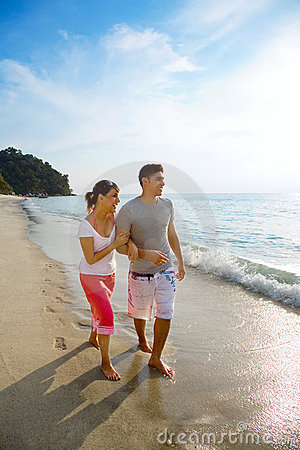 Couple walk along the beach happily