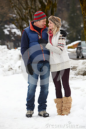 Couple Walking Along Snowy Street In Ski Resort