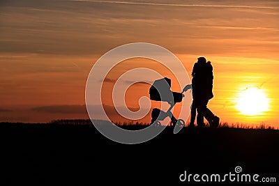 Couple walking baby car sunset