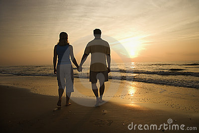 Couple walking on beach at sunset.