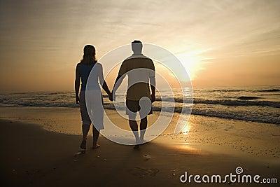 Couple walking on beach at sunset.